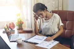Femme d'affaires travaillant avec l'effort au bureau avec l'ordinateur portable et le Doc. images stock