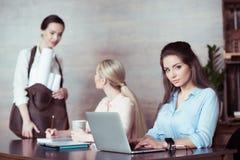 Femme d'affaires travaillant avec l'ordinateur portable avec des collègues derrière Image libre de droits