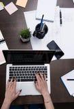 Femme d'affaires travaillant avec l'ordinateur portable sur le dessus de table en bois à l'espace de travail Photographie stock libre de droits