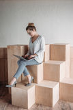 Femme d'affaires travaillant avec l'ordinateur portable tout en se reposant sur les cubes en bois Photo stock