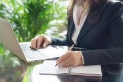 Femme d'affaires travaillant avec un ordinateur portable et une inscription photographie stock libre de droits