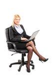 Femme d'affaires travaillant sur l'ordinateur portable posé sur la chaise Photographie stock