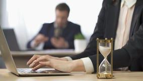 Femme d'affaires travaillant sur l'ordinateur, sablier s'écoulant goutte à goutte, anticipation de résultats clips vidéos