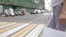 Femme d'affaires traversant la route à un passage pour piétons, dans les mains d'un paquet avec des achats sur le sac d'épaule banque de vidéos