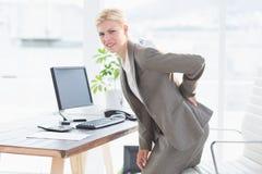 Femme d'affaires triste ayant des douleurs de dos photos stock