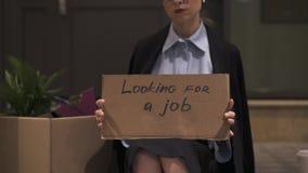 Femme d'affaires triste s'asseyant dans la rue avec le carton recherchant un signe du travail clips vidéos