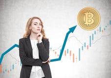 Femme d'affaires d'une chevelure rouge songeuse, bitcoin, graphique photo stock