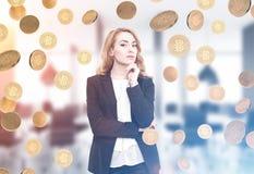Femme d'affaires d'une chevelure rouge songeuse, pluie de bitcoin Images stock