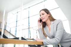 Femme d'affaires Using Smartphone While se penchant sur la balustrade image stock