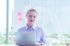 Femme d'affaires utilisant l'ordinateur portable en rencontrant la salle de conférence photographie stock libre de droits