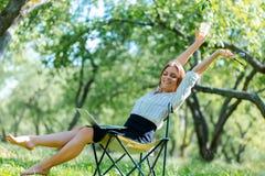 Femme d'affaires utilisant l'ordinateur portable sur la pause de midi en parc de ville et tenir le coffe dans sa main photo stock