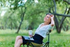 Femme d'affaires utilisant l'ordinateur portable sur la pause de midi en parc de ville et tenir le coffe dans sa main photo libre de droits