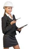 Femme d'affaires utilisant le casque antichoc tenant le presse-papiers Photo libre de droits