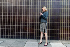 Femme d'affaires vérifiant son téléphone Image stock