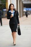 Femme d'affaires Walking Along Street tenant le café à emporter Images stock
