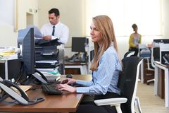 Femme d'affaires Working At Computer dans le bureau occupé photographie stock