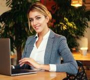 Femme d'affaires Working On Laptop dans le café La jeune femme d'affaires utilise l'ordinateur portable en café Mode de vie et co Photographie stock libre de droits