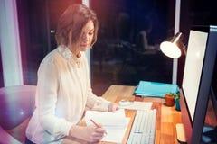 Femme d'affaires Writing On Paper au bureau Photographie stock libre de droits