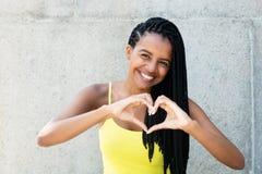 Femme d'afro-américain avec des dreadlocks dans l'amour montrant l'esprit de coeur Photographie stock