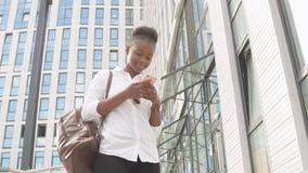 Femme d'afro-américain avec la marche de sac à dos extérieure et parler au téléphone portable banque de vidéos