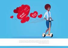 Femme d'afro-américain avec les ballons à air en forme de coeur montant le scooter électrique Valentine Day Concept heureux Photos libres de droits