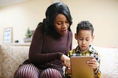 Femme d'afro-américain avec son fils à la maison utilisant le comprimé Photos libres de droits
