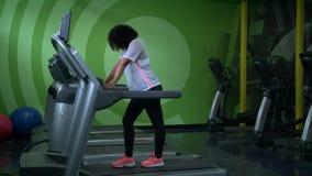 Femme d'afro-américain courant sur un tapis roulant dans le gymnase banque de vidéos