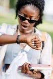 Femme d'afro-américain dans des lunettes de soleil tenant des livres et vérifiant la montre-bracelet Image stock