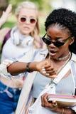 Femme d'afro-américain dans des lunettes de soleil tenant des livres et vérifiant la montre-bracelet Image libre de droits