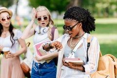Femme d'afro-américain dans des lunettes de soleil tenant des livres et vérifiant la montre-bracelet tandis qu'amies émotives se  Images stock