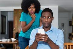 Femme d'afro-américain de jalousie vérifiant la causerie sur le téléphone portable de la BO Photos stock