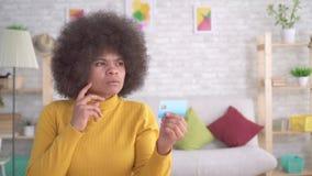 Femme d'Afro-américain de portrait réfléchie et sérieuse regardant la carte de banque dans des ses mains banque de vidéos