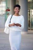 Femme d'afro-américain envoyant le message textuel sur le téléphone portable images stock