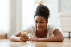 Femme d'afro-américain envoyant un message textuel à un téléphone portable Photo libre de droits