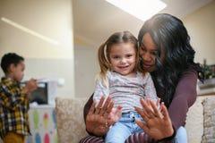 Femme d'afro-américain jouant avec la fille Esprit d'électrodéposition de femme elle Photo libre de droits