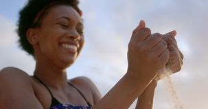 Femme d'afro-américain jouant avec le sable 4k clips vidéos