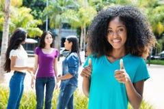 Femme d'afro-américain montrant le pouce avec le groupe d'amies Photos stock