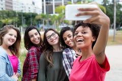 Femme d'afro-américain prenant le selfie avec le groupe d'international Images libres de droits