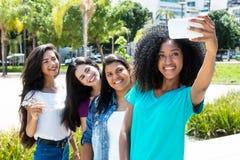 Femme d'afro-américain prenant le selfie avec le téléphone et l'internationa Photos stock