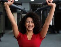 Femme d'afro-américain s'exerçant au gymnase sur la machine photo stock