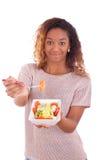 Femme d'afro-américain mangeant de la salade, d'isolement sur le backgroun blanc Image libre de droits