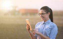 Femme d'agriculteur avec le comprimé dans le domaine photos stock