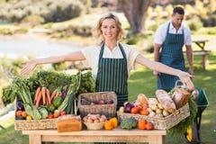 Femme d'agriculteur présent une table de nourriture locale Image libre de droits