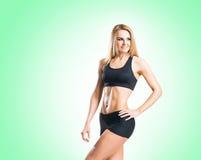 Femme d'ajustement, en bonne santé et sportive dans les vêtements de sport d'isolement sur le blanc Image stock