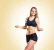 Femme d'ajustement, en bonne santé et sportive dans les vêtements de sport mesurant son corps i Photographie stock libre de droits