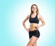 Femme d'ajustement, en bonne santé et sportive dans les vêtements de sport mesurant son corps i Image stock