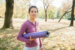 Femme d'ajustement tenant le yoga Mat At Park photo libre de droits