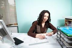 Femme d'architecte à son bureau fonctionnant avec des modèles dans l'avant Images libres de droits