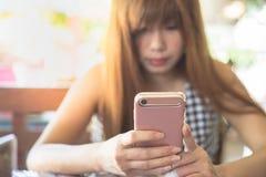 Femme d'ASEAN causant par l'intermédiaire du smartphone rose Photographie stock libre de droits