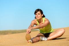 Femme d'athlète étirant la jambe sur la plage Images libres de droits